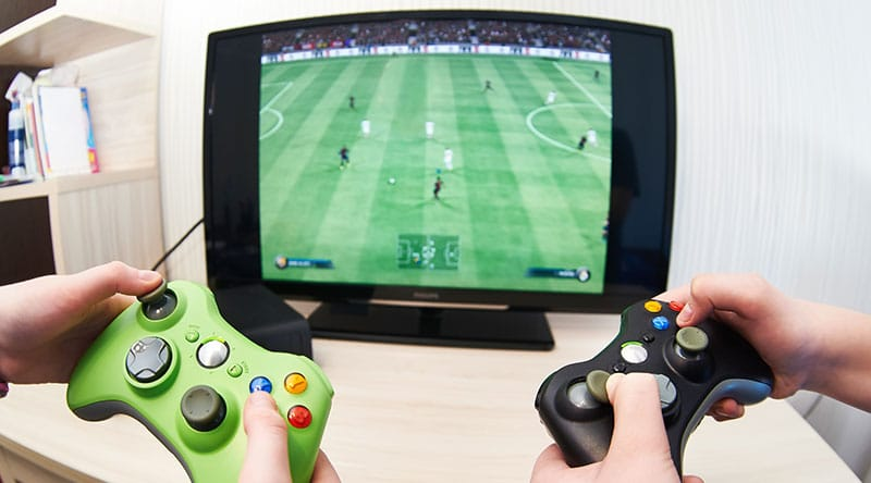 Playing sports video games using gaming controllers